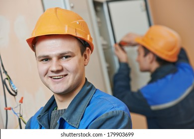 Happy young adult electrician builder engineer in front of his co-worker screwing equipment in fuseboard