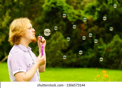 Happy young adult man blowing soap bubbles in nature green spring park.