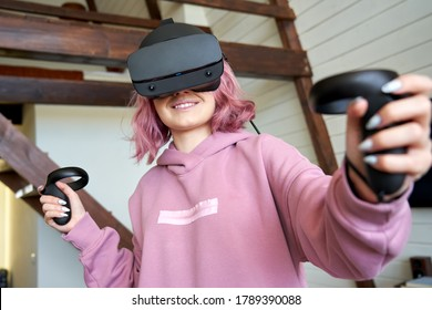 Happy young adult woman gamer teen girl pink hair wear vr headset goggles hold controllers play video game simulator immersive futuristic virtual reality 3D vr tour, watch 360 video, stand at home.
