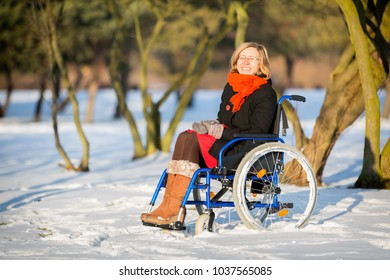 happy young adult woman on wheelchair in the snowy park in winter at sunset