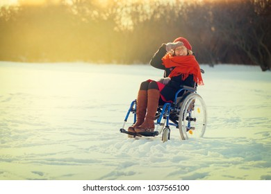 happy young adult woman on wheelchair in the park in winter at sunset