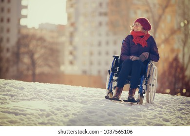 happy young adult woman on wheelchair in the city in winter at sunset