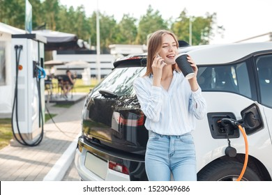 Happy young adult woman smiling wide, looking away, charging automobile battery from small public station, standing near electric car, drinking coffee and talking on smartphone