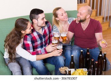 Happy young adults drinking beer and laughing at home