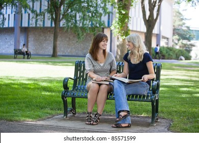 Happy young adults sitting on bench on college campus