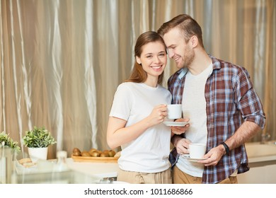Happy young affectionate couple with tea enjoying morning in the kitchen