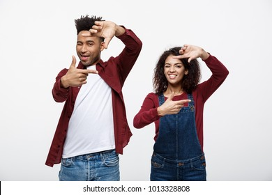 Happy young African American couple looking through a finger frame and smiling while standing isolated on white