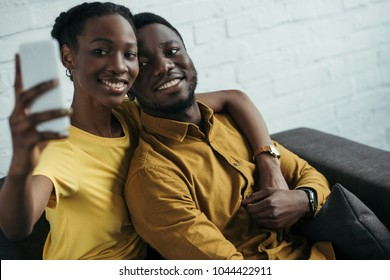 happy young african american couple taking selfie with smartphone