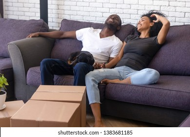 Happy young African American couple rest on cozy couch together with favorite pet companion, have break relocating to new home, excited black family with dog relax on sofa glad to move in own house