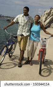 Happy young African American couple with bicycles walking on beach