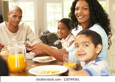 Happy young African American family seated around a table enjoying a healthy breakfast together in a relaxed start to the day