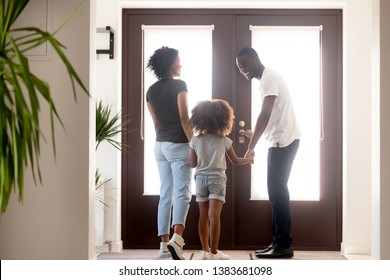 Happy young African American family stand in hallway hold hands go out for a walk, smiling millennial black dad open doors, taking wife and daughter outside have fun. New beginning concept