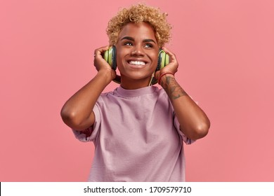 Happy young African American female relaxed with a great song has broad smile, touches headphones, listens to music, dressed in a lilac casual t shirt, isolated over pink studio wall, wants to dance.