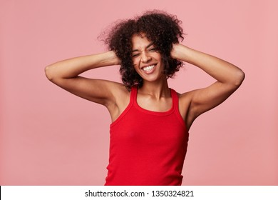 Happy young african american girl enjoys dancing, winks,enjoys the rest time, smiles lively, touches her curly afro hair, holds her hands to her head, has fun,wearing red singlet, isolated on pink