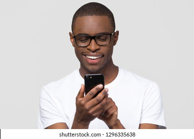 Happy young african american man in glasses using smartphone gadget social media apps, smiling black guy user holding cellphone texting sms on mobile phone isolated on white grey studio background