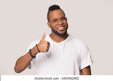 Happy young African American man in glasses showing thumbs up like gesture, look at camera, smiling male student, satisfied client customer recommend good service, isolated on grey studio background