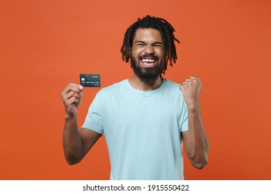 Happy young african american man guy wearing blue casual t-shirt posing isolated on bright orange wall background studio portrait. People lifestyle concept. Hold credit bank card doing winner gesture