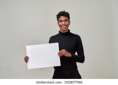 Happy young african american man holding blank bill and smiling at camera while posing on light background. Discount and sale concept