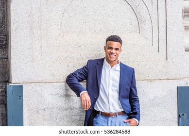 Happy Young African American Man in New York. Wearing blue blazer, white shirt, a handsome black male college student standing against vintage wall on campus, smiling. Color filtered effect.