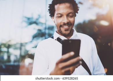 Happy young African American man in headphone checking email box at sunny city and enjoying to listen to music on his electronic mobile device.Blurred background