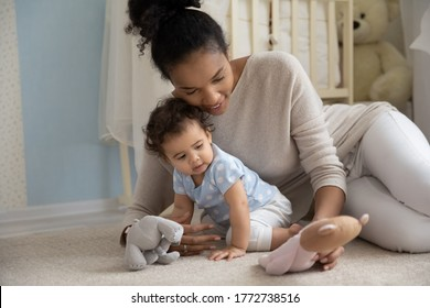 Happy young African American mother playing with toddler daughter with stuffed toys, lying on warm floor with underfloor heating at home, enjoying playtime together, childcare and upbringing