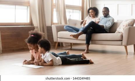 Happy young african American parents sit relax on couch watch busy little children lying on floor playing together, black family with preschooler kids enjoy rest in living room spend weekend at home