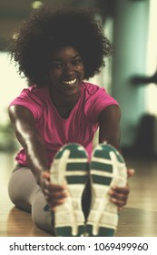 happy young african american woman in a gym stretching and warming up before workout