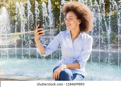 Happy Young African American Woman In Casual Wear, Using Smartphones For Social Network , Outdoor Portrait, Afro Curly Hairstyle, Looking At The Phone