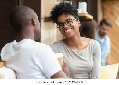 Happy young african american woman smiling enjoy fun conversation with man friend boyfriend, mixed race teen girl in love talk laughing flirting at meeting, black couple on first date outdoor concept