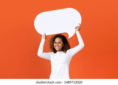 Happy young African American woman in plain white long sleeve t-shirt holding empty speech bubble isolated on orange  background - Shutterstock ID 1489713020