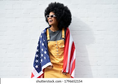Happy young African American woman wrapped in USA flag laughing standing against white wall. Smiling free mixed race gen z hipster girl with Afro hair celebrating freedom on Independence Day concept.