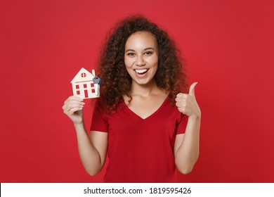 Happy young african american woman in casual t-shirt hold house bunch of apartment keys, showing thumbs up isolated on red background studio portrait. People lifestyle concept. Mock up copy space.