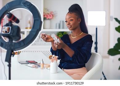 glückliche junge afrikanische Amerikanerin, die einen Schönheitvlog von zuhause durchströmt, Online-Content-Ersteller, der einen Parfüm-Duft anwendet