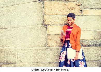 Happy Young African American Woman texting on cell phone outside in New York, wearing orange red jacket, flower patterned skirt, carrying laptop computer, standing by stone wall on campus, smiling.