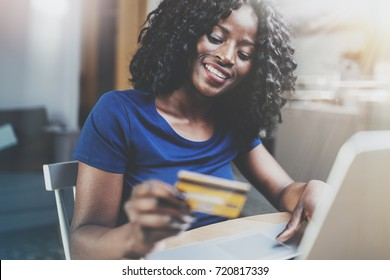 Happy young african american woman shopping online through laptop using credit card at home. Horizontal,blurred background.Cropped