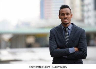 Happy young African businessman smiling in the city streets outdoors