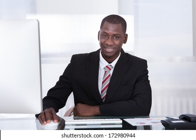 Happy Young African Businessman Using Computer At Desk