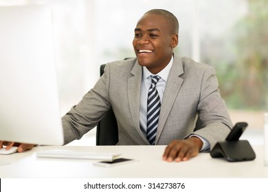 happy young african businessman working on computer