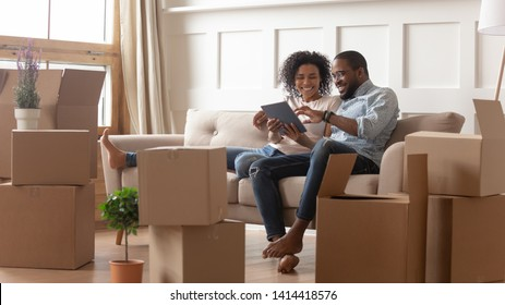 Happy young african couple use digital tablet discuss interior design renovation ideas sit on sofa on moving day, black new house renters owners tenants relax on couch with boxes having fun online