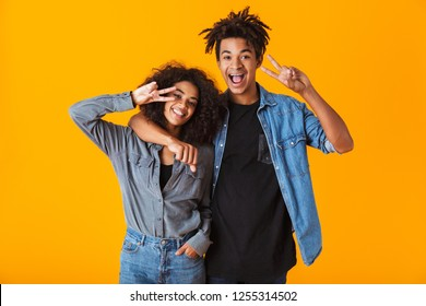 Happy young african couple wearing casual clothes standing isolated over yellow background, showing peace gesture
