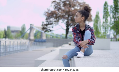 Happy young african female college student sitting outdoors.