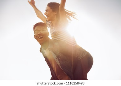Happy young african man carrying his friend on his back on a bright sunny day. Friends enjoying piggyback ride outdoors.