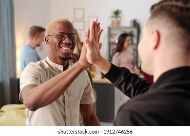 Happy young African man in casualwear and eyeglasses giving high five to his Caucasian friend at party while looking at him with toothy smile