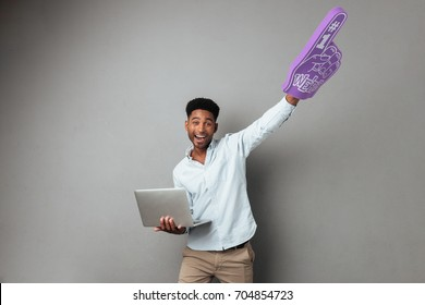 Happy young african man holding laptop computer and foam finger isolated over gray background