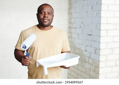 Happy young African man with paintroller and white plastic container with paint standing against two walls in his new flat or house