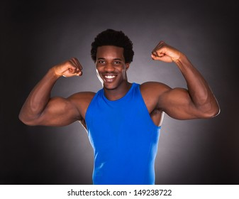 Happy Young African Man Showing Muscle Over Black Background