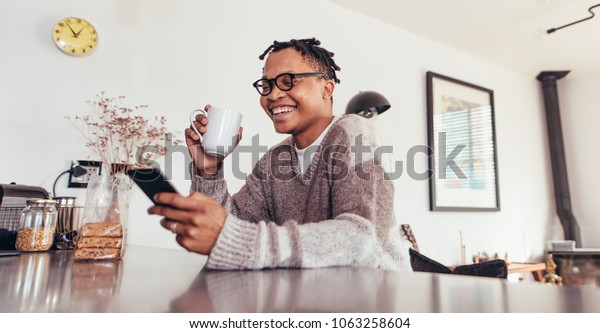 Happy young african man sitting at table using mobile phone and drinking coffee. Man relaxing at home reading text message on his cell phone in morning.