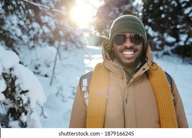 Happy young African man in sunglasses and warm winterwear standing in front of camera against firtrees in snow during chill on winter weekend