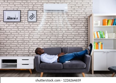 Happy Young African Man Using Laptop Enjoying Cooling Under Air Conditioner At Home