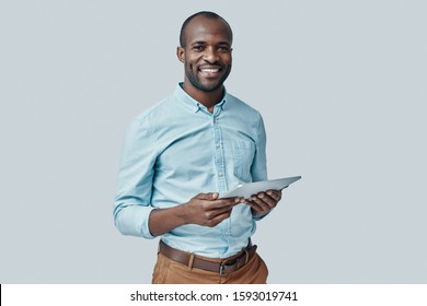 Happy young African man using digital tablet and smiling while standing against grey background